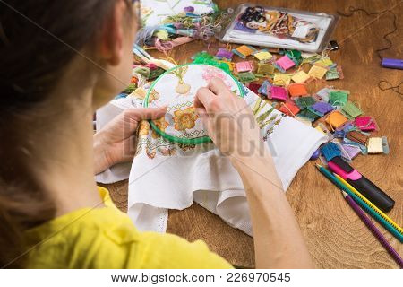 Girl Sitting At A Table Where Everything Necessary For Embroidery, Embroiders A Bigger Picture. Copy