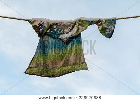 Colorful Sweater, Laundry With Snow On It, Drying On The Clothesline In The Winter. Blue Sky And Whi
