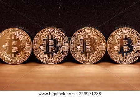 Four Golden Bitcoin Coins Virtual Moneyon Wooden Background