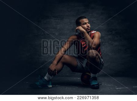 Full Body Portrait Of A Black Basketball Player Sits On A Floor And Holds Basket Ball.