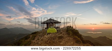 Romantic Sunset Scenery At Herzogstand Mountain, Pavilion And Camping Tent At The Summit. Bavarian A