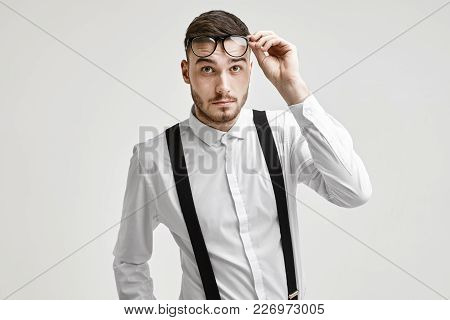 Close Up Shot Of Trendy Looking Hipster Guy With Trimmed Mustache And Stubble Posing Isolated At Whi