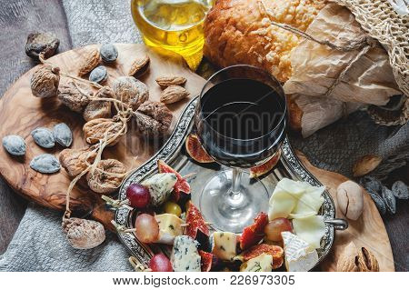 A Glass Of Red Dry Wine And Focaccia Italian Bread With Cheese And Olive Oil, Sun-dried Tomatoes And