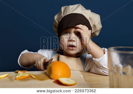 Portrait Of Adorable Little Girl In Chef Headwear And Apron Cutting Oranges On Cooking Board Using K