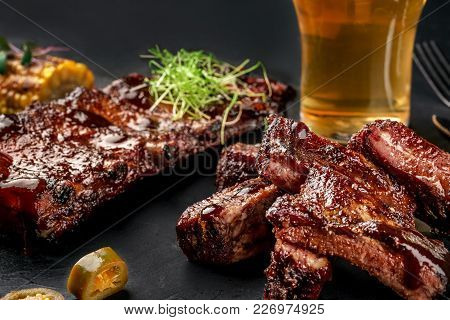 Pork And Beef Ribs In Barbecue Sauce And A Glass Of Beer On A Black Slate Dish. A Great Snack To Bee