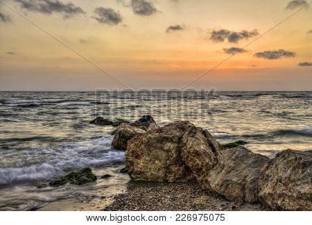 Dramatic Sunset Over Tremble Sea Waves, With Rocky Seashore, Israel