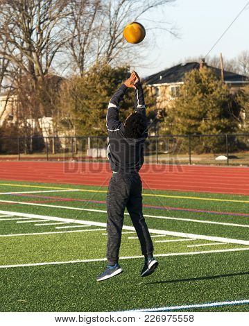 A High School Track And Field Athlete Is Jumping In The Air While Throwing A Medicine Ball Over His
