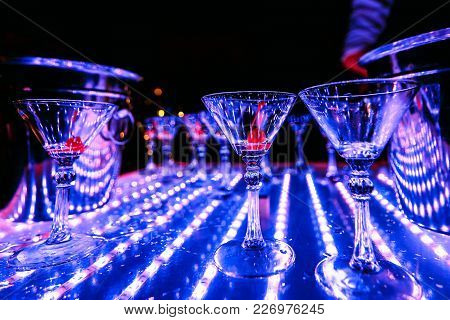 Glasses Of Alcoholic Cocktails On The Colorful Bartender Show In The Restaurant Illuminated By Ultra