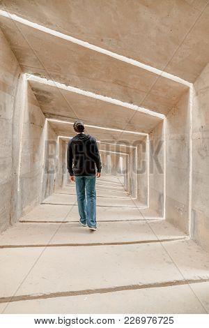 Back View Of Man Walking Alone In Tunnel Corridor. Urban Underground Lonely Walkway  Passage. Single