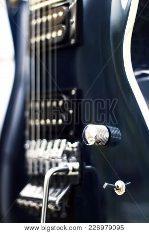 Detail Of A Black Electric Guitar Low Key With Soft Light And Depth Of Field .