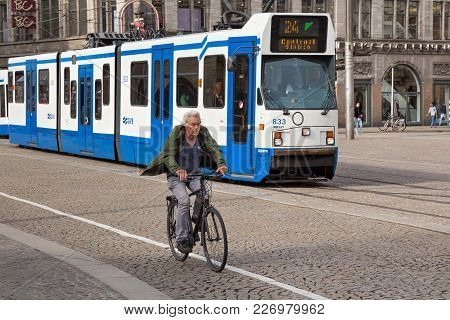 Amsterdam, Netherlands - June 25, 2017: Elderly Man On A Bicycle Next To A Passing Bn Constructions