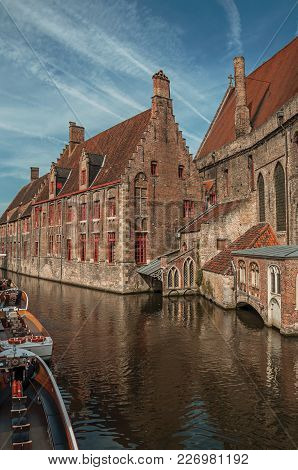 Old Buildings On The Canal Bank, Boats And Sunny Blue Sky In Bruges. With Many Canals And Old Buildi