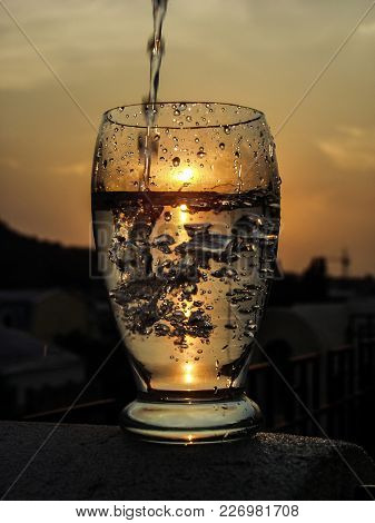 A Full Glass Of Water With A Pouring Waterjet And A Sun  Downing Inside.