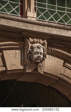 Close-up Of Decorative Sculpture In Human Shape On A Gothic Building At Bruges. With Many Canals And