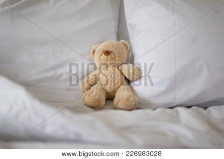 Sleeping Brown Teddy Bear On White Bed.