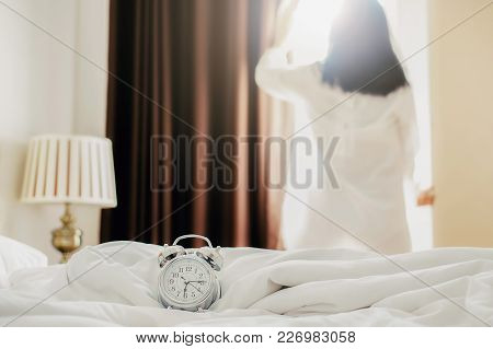 Alarm Clock Standing On Bedside Table Has Already Rung Early Morning To Wake Up Woman Is Stretching