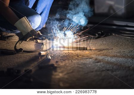 Selective Focus At Right Hand And Motion Blur. Low Light Image Of Welder Or Craftsman In A Welding M