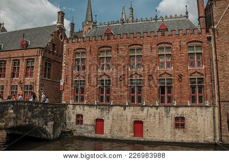 Bruges, Belgium - July 05, 2017. People On Bridge And Old Buildings At Canal In Bruges. With Many Ca