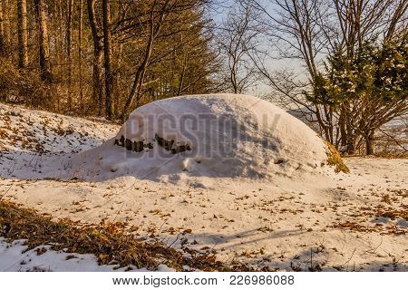 Winter Landscape Of Unmarked Burial Mound Covered With Snow In Woodland Area With Trees In Backgroun