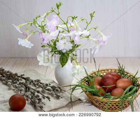 Easter Eggs And Bouquet Of Petunias On A White Table.