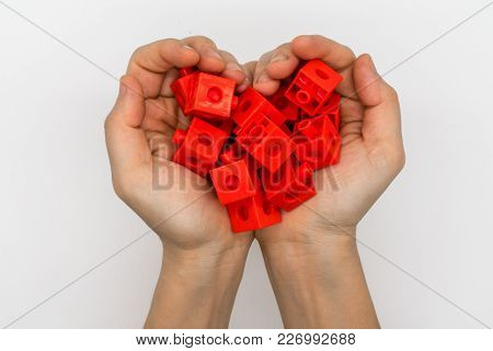 Hands Holding Red Plastic Blocks Creating Heart Shape Isolated On White