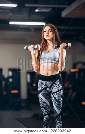 Athletic Girl Does Exercise With The Weight In The Gym