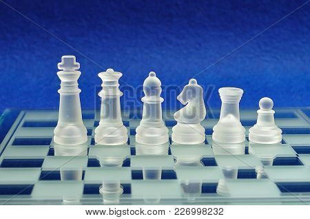 Different Chess Pieces Displayed On A Glass Chessboard With A Blue Background