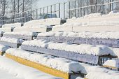 Seats in the stadium under the snow. Chairs for spectators at the stadium under the snow. Snow on the seats. poster