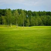 A lush fairway in the foreground contrast in the distance at a golf course. poster