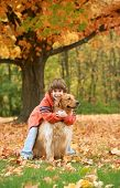 Boy Giving Golden Retriever a Hug under a Beautiful Fall Tree poster