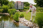 Retirement - feeding fish outdoor in garden pond poster