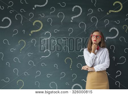 Serious Business Woman In Front Of Question Marks Drawn On Blackboard
