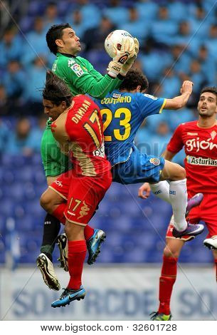 BARCELONA - APRIL 28: Juan Pablo Colinas(C) of Gijon block the ball between Damian(L) and Coutinho(R) during a Spanish League match at the Estadi Cornella on April 28, 2012 in Barcelona, Spain