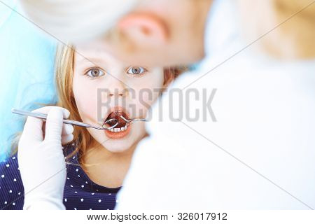 Little Baby Girl Sitting At Dental Chair With Open Mouth During Oral Check Up While Doctor. Visiting