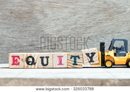 Toy forklift hold letter block y to complete word equity on wood background poster