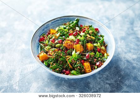 Hokkaido pumpkin and quinoa salad with kale, pomegranate, spring onion and toasted sunflower seeds. Healthy homemade food. Vegan food