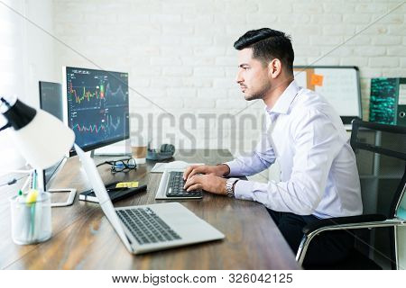 Confident Young Male Stock Broker Trading Through Computer At Desk