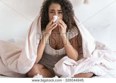 Worried International Woman Wiping Her Nose With Serviette