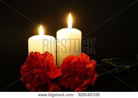 Two Burning Candles With Flowers. Condolences Over The Bereavement. Fire Of Regret For Irretrievable