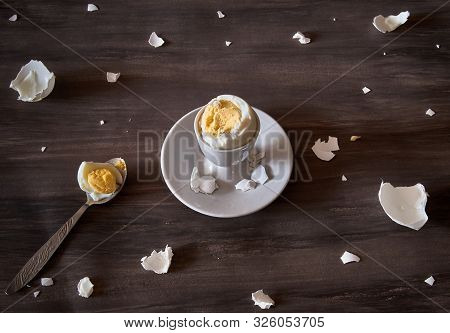Breakfast still life. Boiled soft-boiled egg on a stand with a spoon, with pieces of eggshell. The view from the top. poster