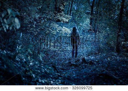 Woman Walking Alone On Path In Mystic Dark Forest. Lonely Adult Girl In Strange Creepy Park At Night