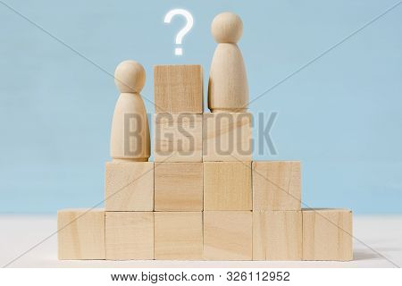 Abstract Wooden Faceless Figures Of Two Men On Career Stairs With Painted Question Mark Over Upper S