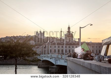 Lyon, France - July 14, 2019: Man Waiving An Algerian Flag In The Center Of Lyon, With Landmarks Suc