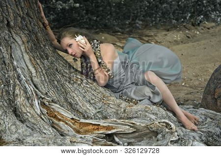 Woman Listens To The Noise Of A Seashell Lying On An Old Tree