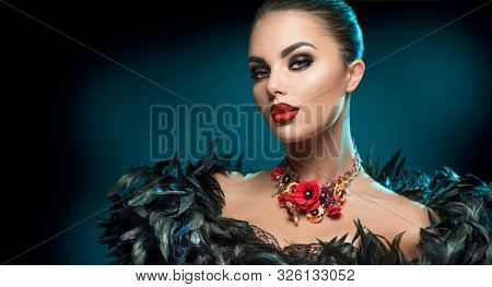 High Fashion Model Girl Portrait with Trendy gothic make-up, Black Hair style, Make up, dark accessories. Halloween Vampire Woman portrait with black smoky eyes, feathers dress, over black background