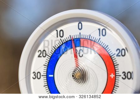 Outdoor thermometer with Celsius scale showing cold minus 4 degrees temperature - dramatic weather change or cold wave concept