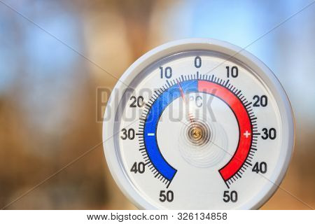 Outdoor thermometer with Celsius scale showing cold minus 5 degrees temperature - dramatic weather change or cold wave concept