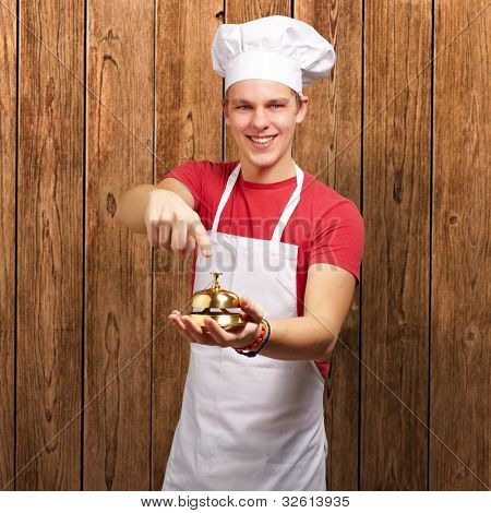 portrait of a young cook man pressing a golden bell against a wooden wall