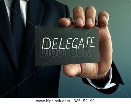 Delegate Sign In The Hands Of A Businessman. Delegation Concept.