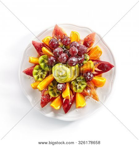 Top view of fruit plate with orange wedges, apple, grapes, kiwi and pear isolated. Vegan platter with sweet sliced fruits, healthy and delicious breakfast topview